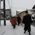 角巻やトンビを着て雪の高田を歩く